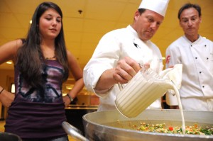 Got milk? · Sarah Kelly (left), a freshman majoring in cinema-television production, looks on as Thomas Moran (center),  associate executive chef at USC, cooks a vegetarian dish at EVK Wednesday. The demonstration was part of an initiative that aims to increase the availability of vegetarian options. - Young Kim | Daily Trojan