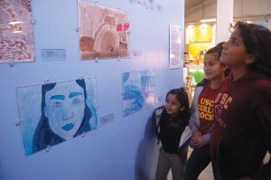 Color me · Kimberly Gramajo (left), Otrilia Gramajo and Evelin Esparaza, all local students, view the art work on display at the current Art in the Village exhibit in the University Village. - Alejandra Vargas-Johnson | Daily Trojan