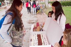 """Giving back · Tiffany Chu, a junior majoring in gerontology, receives a cupcake from Cindy Le, the lead coordinator of """"Clothes for Cupcakes,"""" for donating a t-shirt on Trousdale Parkway on Thursday. - Austin Vogel 