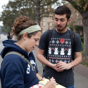 Activism ·  Junior Matthew Shoemaker (right), a member of SCALE, talks with Leanne Tracy (left), a missionary, as she signs the petition. - Ralf Cheung | Daily Trojan