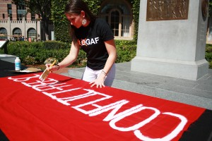 """Conflict-Free 'SC · Sophia Geanacopoulos, a sophomore majoring in international relations, paints a banner during the """"Come Out for Congo"""" rally, which took place on Wednesday, March 12, in Hahn Plaza. - Hailey Sayegh 