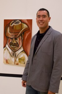 "Hidden talent · Sergeant Rick Gonzales poses next to his painting, ""The Mexican,"" at the art exhibit ""Beyond the Badge"" in the Galen Center. - Austin Vogel 