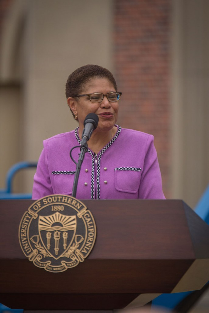 Karen Bass stands behind a USC podium and speaks at an event in the USC Village.