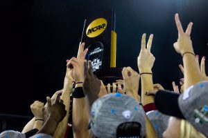 The victorious Trojan team holds the NCAA Championship trophy aloft, putting two fingers in the air in a salute to USC tradition - Photo courtesy Madeleine Roche