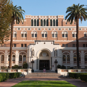 This is a front view of the entrance to Doheny Memorial Library. It is a sunny afternoon and the half of the building is in the shade.