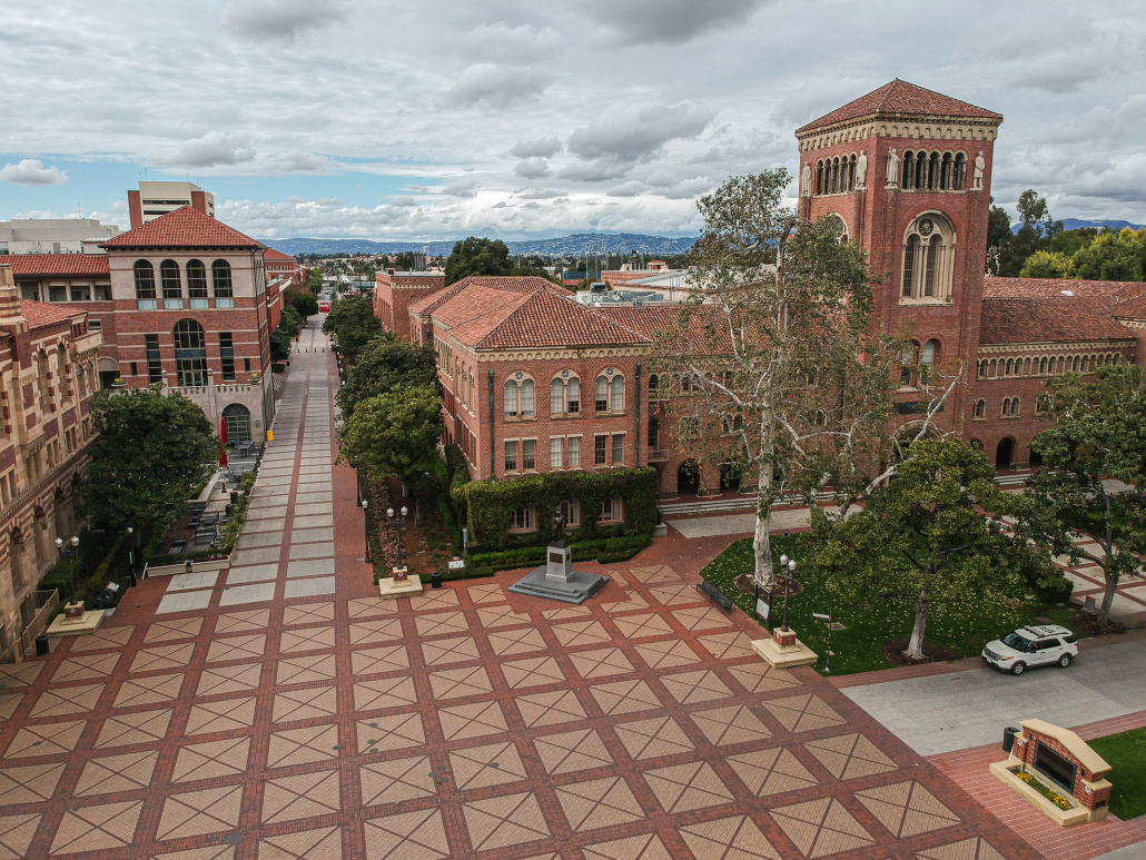 A partially gray-clouded sky overlooks the russet bricked buildings of Bovard Auditorium, the Student Union, Ronald Tutor Campus Center and the red and tan squared design of Hahn Plaza. A Department of Public Safety Cruiser sits in front of Bovard and the empty courtyard.