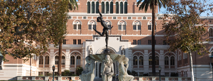 This is a photo of the fountain at the center of Alumni Park at USC. In the background is Doheny Memorial Library, partially in the shade on a bright sunny day.