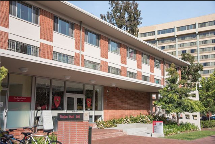"""Photo of Trojan Hall residence hall, a red brick building with glass doors and windows and a sign in front reading """"Trojan Hall 101."""" There is another building, trees and blue sky in the background."""