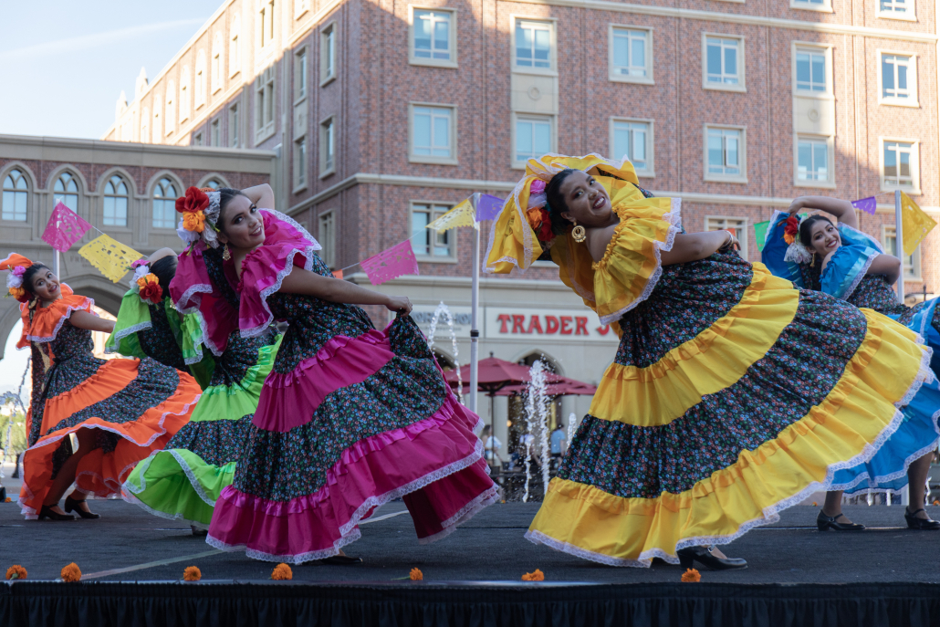 Grupo Folklórico de USC in their Día de los Muertos Showcase in 2019 that was held in the USC Village. Performers are dressed in vibrant, vestuarios as they strike a pose and smile towards the audience. Papel picado hang in the background of the dancers, with orange marigolds surrounding their feet.