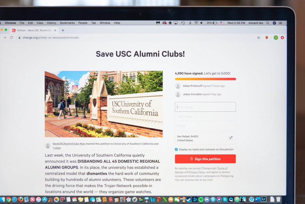 """Photo of the change.org petition created by USC Regional Alumni Group Leadership calling for USC and the USC Alumni Association to reverse the new model and reinstate alumni clubs. The photo displays a portion of a Macbook Air screen and shows more than 4,500 signatures and """"Save USC Alumni Clubs"""" in bold above a picture of an entrance to the USC Village, with a student with a gray backpack walking past."""