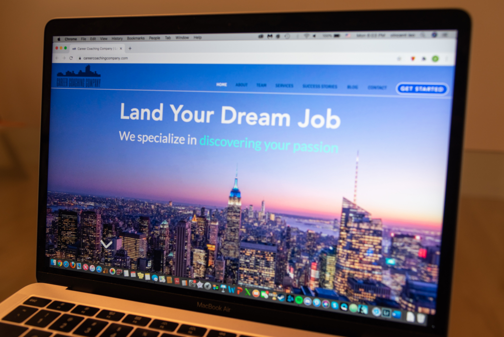 """A side angle photo of a MacBook Air with the screen displaying the landing page of the website www.careercoachingcomapny.com. The page reads the words """"Land Your Dream Job"""" in white text and the background is a photo of the Empire State Building and many other lit up buildings during sunset. The company's logo is in the top right corner and the top is the menu bar including eight tabs including some that read """"About,"""" """"Services"""" and """"Contact."""""""