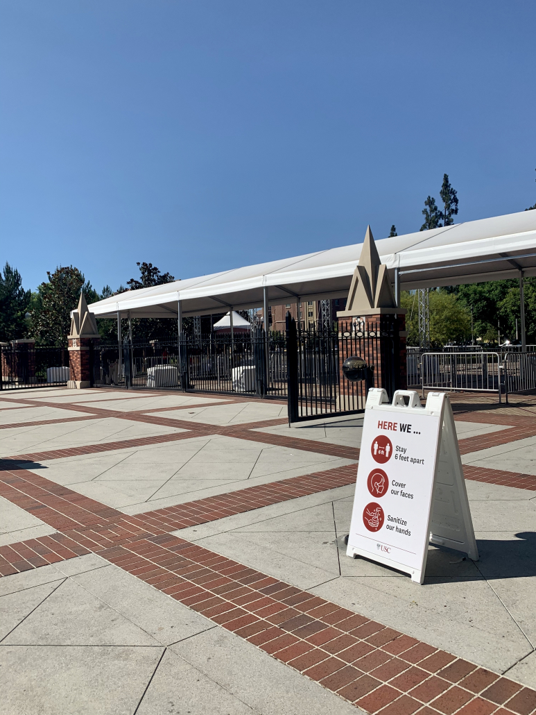 Photo of a gated entrance to campus with a sign including precautionary procedures and blue sky in the background