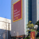 """Photo of the Keck School of Medicine, a tall gray building with a banner reading """"Keck School of Medicine of USC."""" There are stairs leading up to the building, surrounding foliage, another building, and a blue sky in the background."""