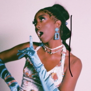 Rapper Flo Milli stands in front of a light pink background looking to her right. She dons baby blue gloves and matching dangling earrings. She's wearing a white printed dress and matching chokers and assorted necklaces. Her hair is pulled up into a long ponytail.