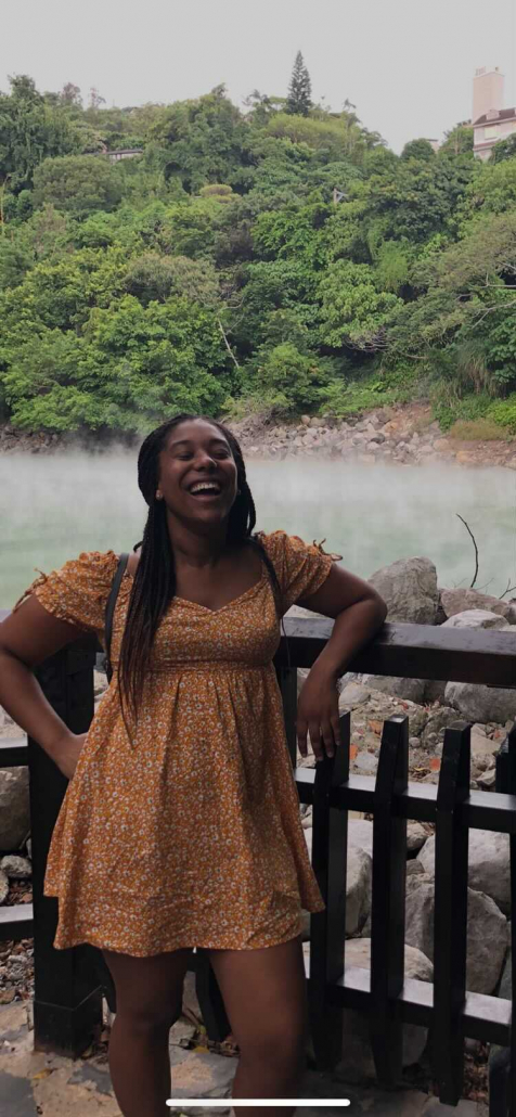 Photo of Jaya Hinton leaning on a brown, wooden fence. The picture /captures/ Hinton in mid-laugh with her eyes closed. In the background, a hill of various green-tinted trees lead into a bed of rocks, slightly hidden through a white mist of fog.