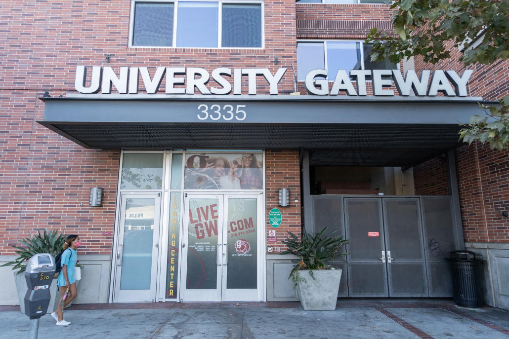 """An image of the Gateway Apartments entrance with a gray sign reading """"University Gateway."""""""