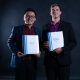 """Photo of Brian Femminella and Travis Chen holding binders that read """"SoundMind Solutions."""""""