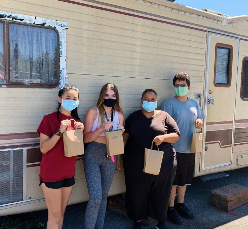 Four people standing with brown paper bags wearing masks