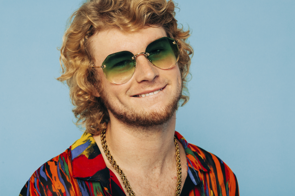 Yung Gravy with a gold chain and green shades, smiling in front of a light blue background.