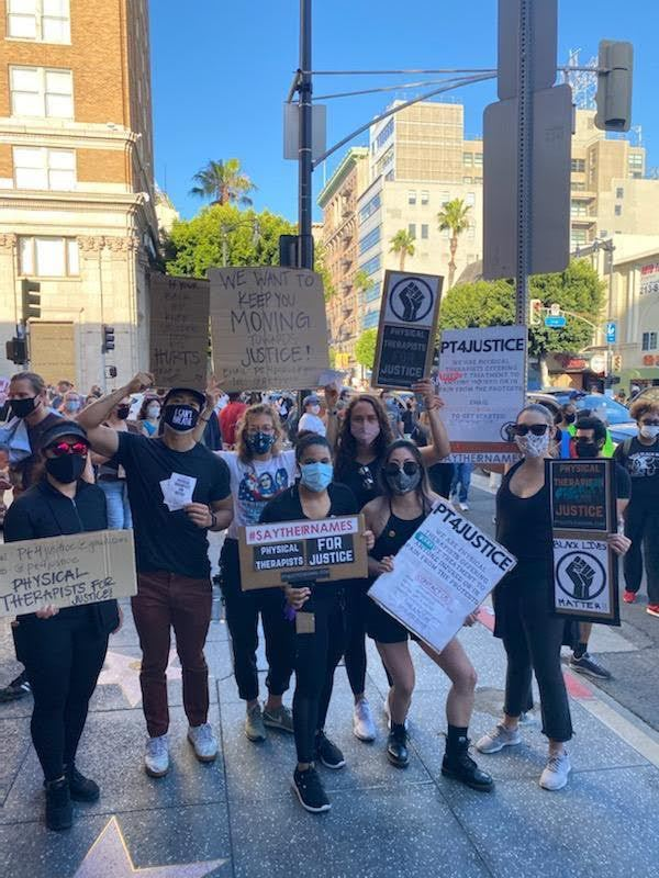 A picture of protestors posing in front of a camera, wearing masks and holding various posters related to the Movement Network and the BLM protests.