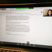 """Photo of a Mac laptop screen showing a document, with the right displaying the title """"Resolution in Support of BIPOC students."""" A small window showing Undergraduate Student Government Vice President Trinity Moore is to the right."""