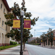 """A sidewalk on campus with banners on lampposts telling people to """"Mask up"""". On the left is the yellow building of the school of cinematic arts and next to the road is the red building of the uytengsu aquatic center"""