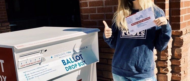 Emily Drysdale standing in front of a red brick wall next to a ballot drop box holding a mail-in ballot in her hand