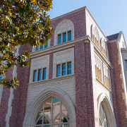 A photo of the red-brick building of the new Annenberg with tree branches