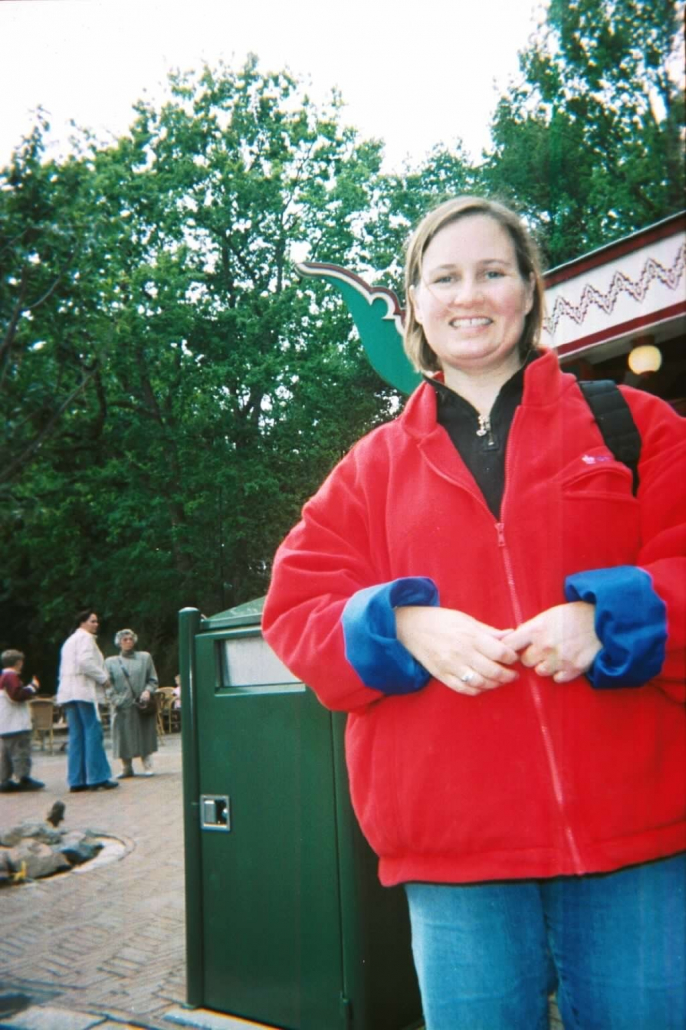 Jennifer Van Loy wearing a red fleece standing in front of trees