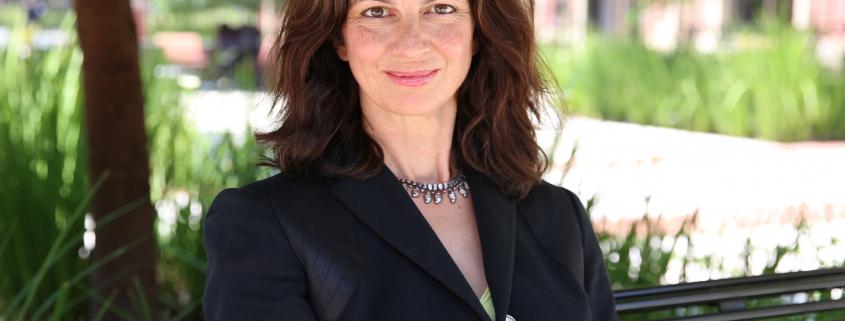 A medium shot of Sarah Gualtieri sitting on a green branch in a blazer