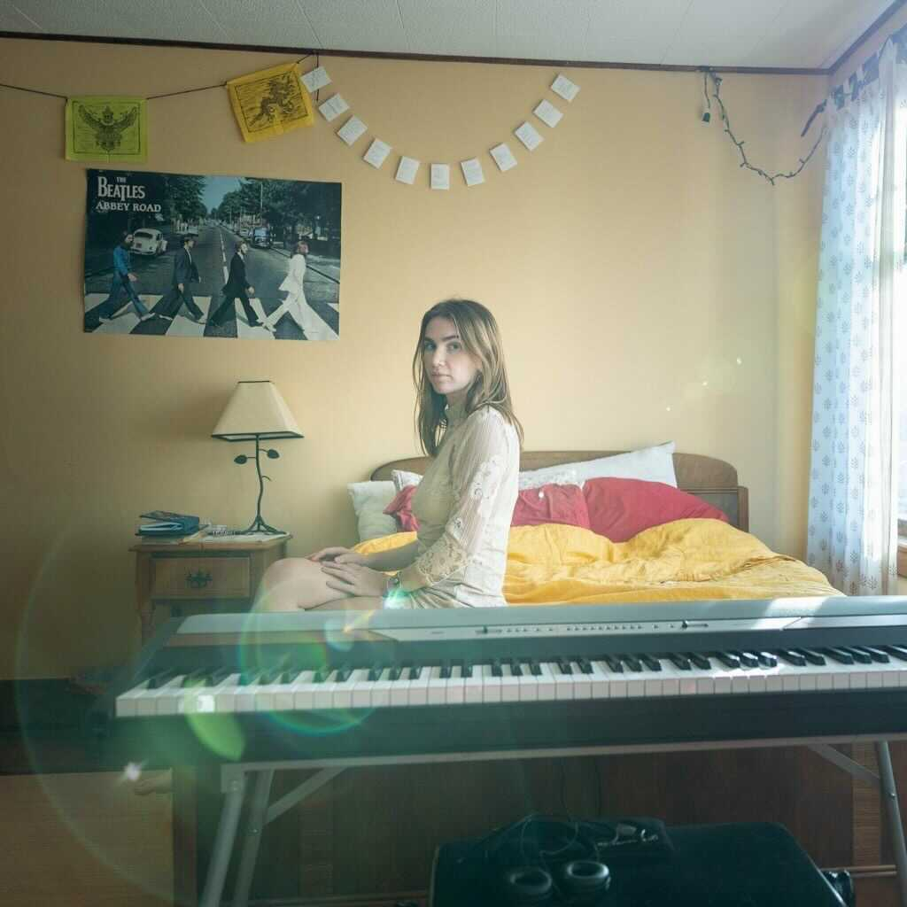 Lila Forde sits on her bed which has yellow sheets and red and white pillows. She is facing the viewer and is wearing a white dress. The wall behind her is yellow and has a poster of the Beatles crossing Abbey Road. A keyboard is in front of the bed.