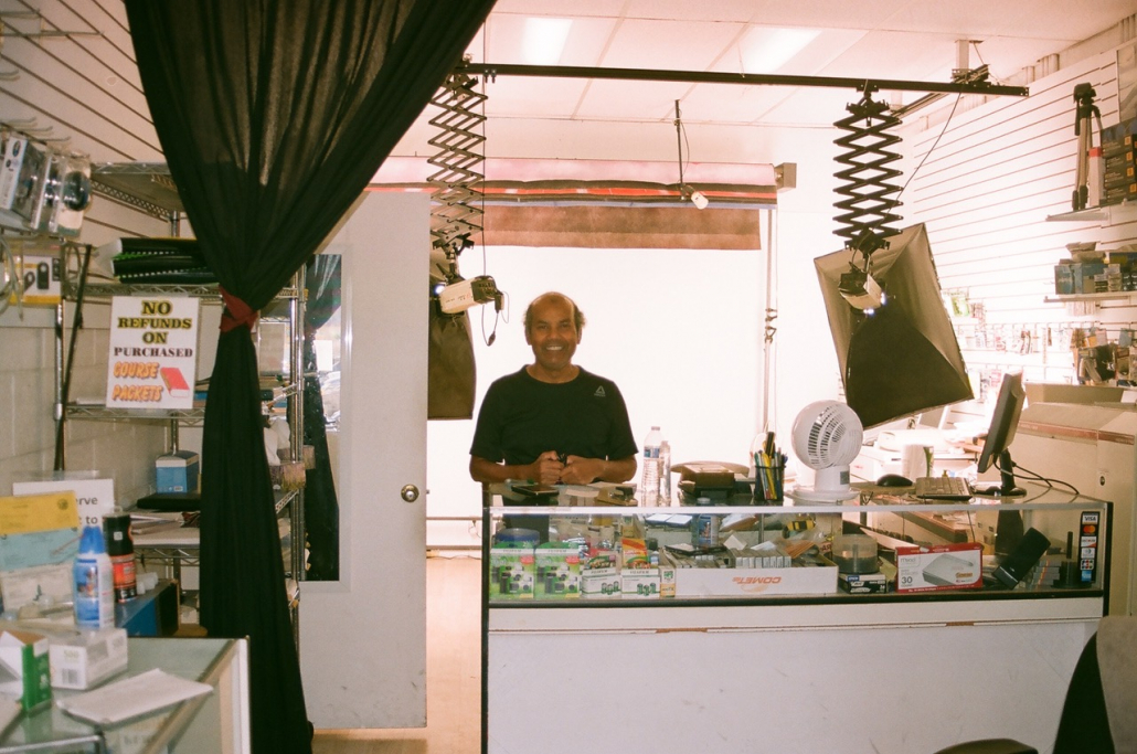 Akm Alam stands inside of his store, Quik-Pix. The store is filled with photography gear.
