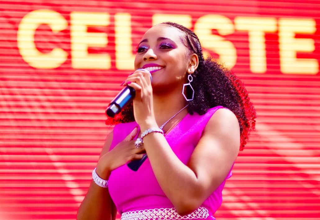 """Celeste stands in front of a red backdrop with the words """"Celeste"""" in bright yellow letters. She is wearing hot pink and is holding a microphone."""