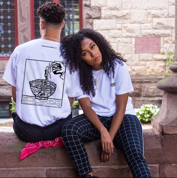 "Two people side by side, the one to the left is turned around to show the back of shirt which has a ramen bowl with depictions of COVID on it, saying ""WHO is going to save US?"" on the bottom."