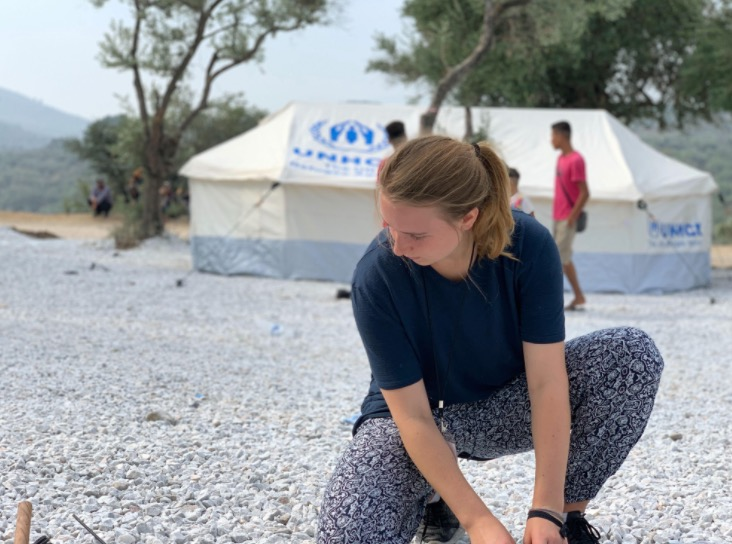 Photo of Laura Roed crouching and looking down at the pebble filled ground. A white and blue tent and multiple figures are behind Roed.