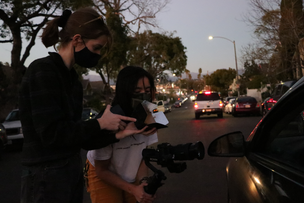 Carolyn Knapp and Izzy Rael film on the set of Eliza McLamb's Pontiac music video in Los Angeles, wearing masks.