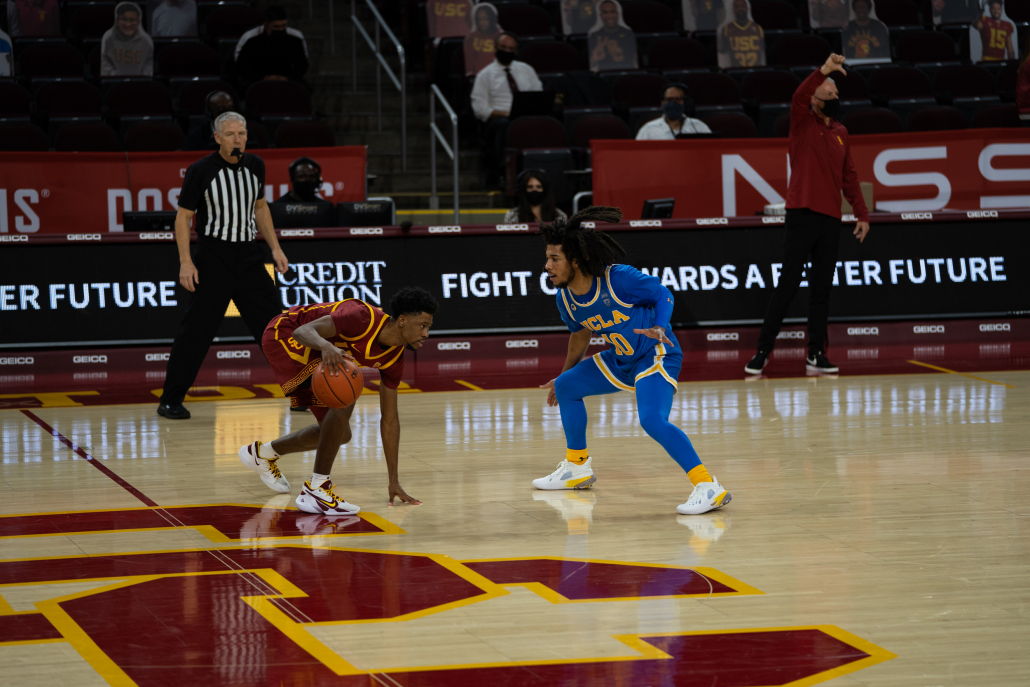 Tahj Eaddy dribbling the ball against UCLA while planting his left hand on the court.