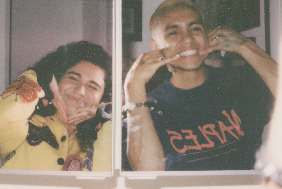 Remi Wolf (left) and Dominic FIke (right) smile and pose in the mirror.