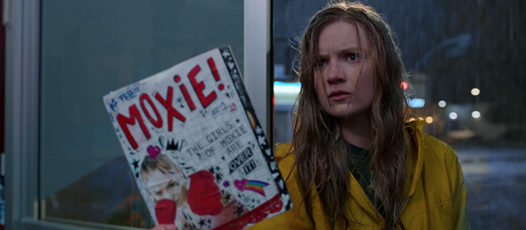 Vivian stands in the rain with a copy of Moxie! in her hand.