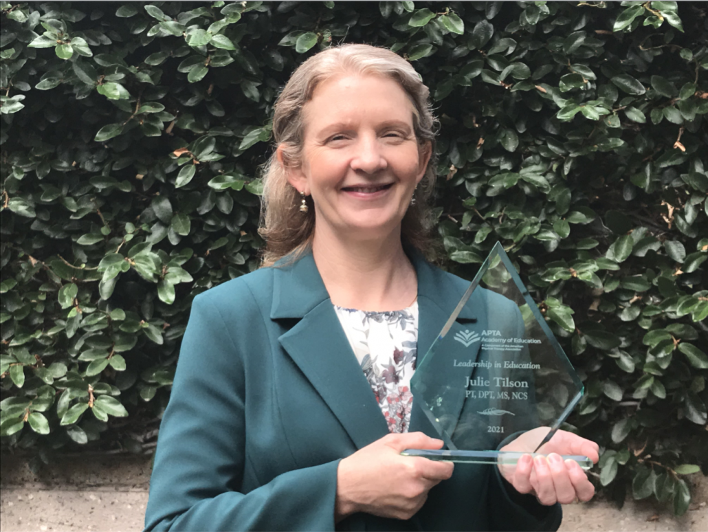 Julie Tilson poses with her award from the APTA for leadership in education.