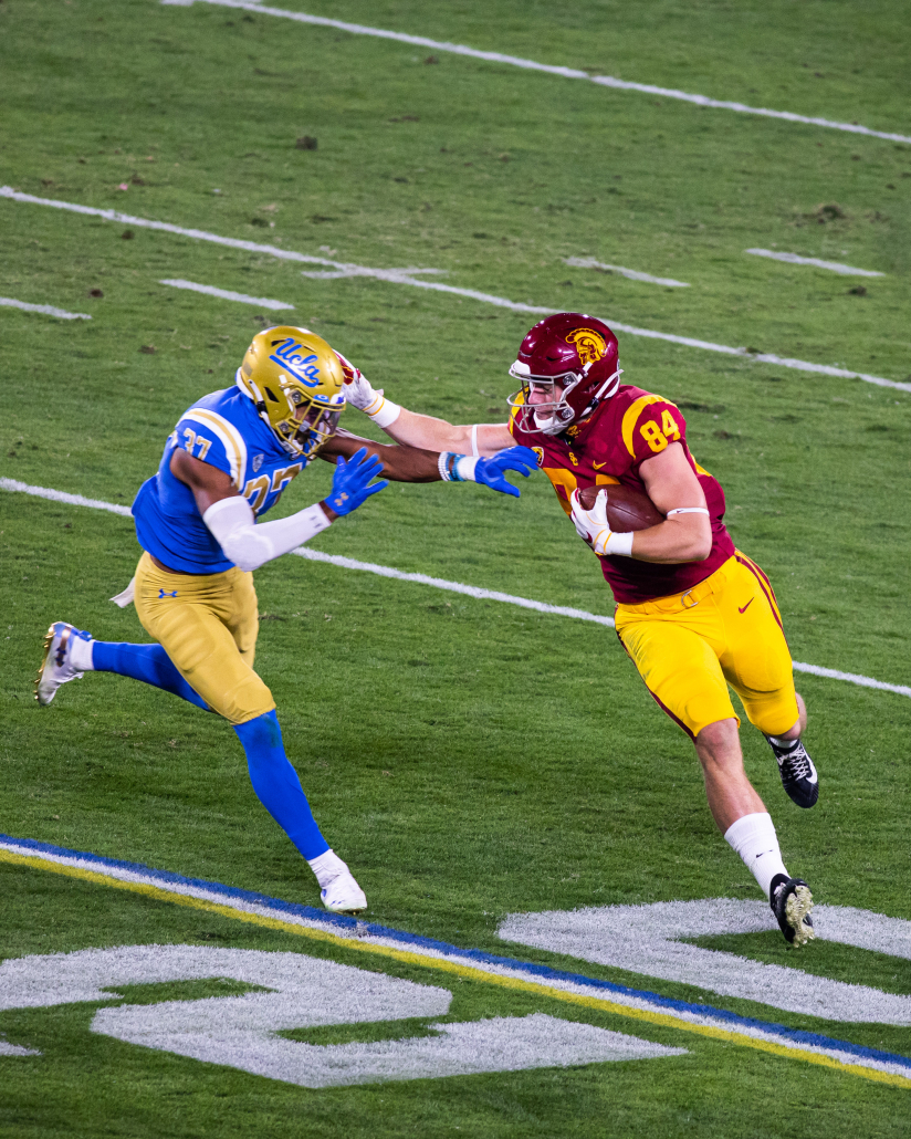 Tight end Erik Krommenhoek stiff-arming a UCLA defender in order to avoid a tackle.