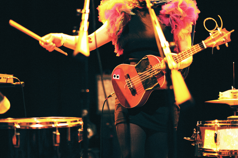 A person is wearing a dress with hot pink ruffles. They are holding a guitar and are drumming along.