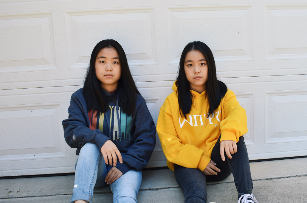 JaJa and JoJo Tong sit next to each other in front of a garage.