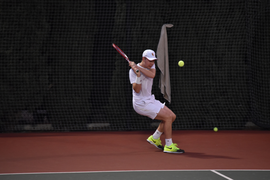 Lodewijk Westrate hits the ball behind the service line while dressed in all white USC gear.
