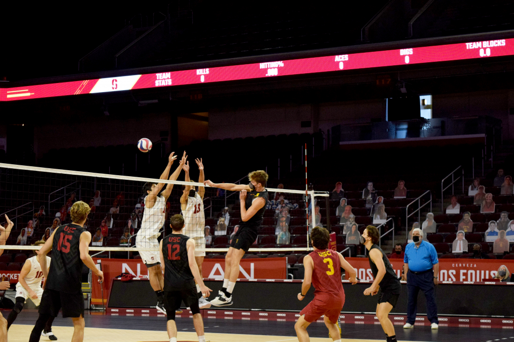 outside hitter Billy Fauntleroy hits the ball over two blockers from the right side of the net