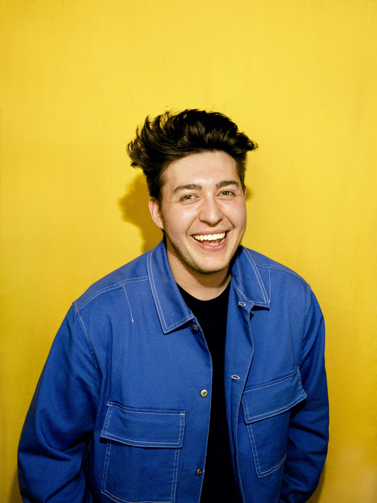 Carlo Rincón poses in front of a yellow background.