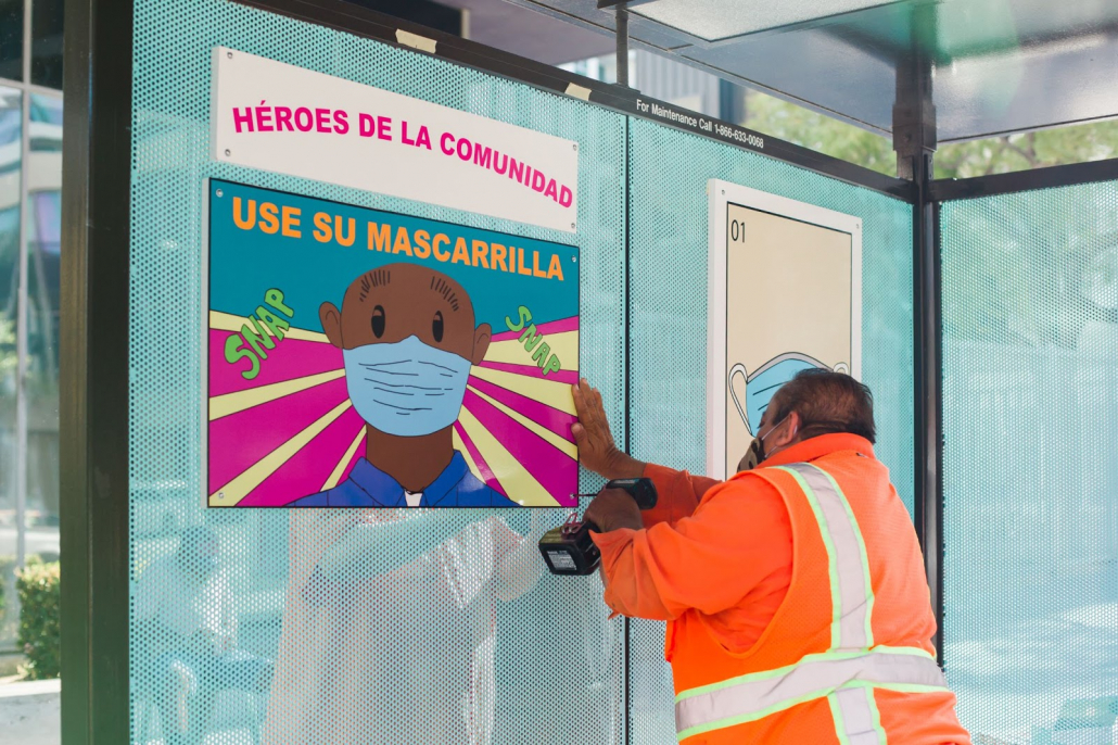 A worker drills a sign with a person wearing a face mask to a bus stop.
