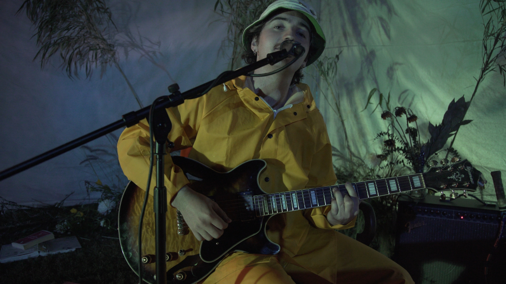 Kid Hastings sits on a stool, wearing a yellow suit while playing the guitar and singing. A background with plants is shown.