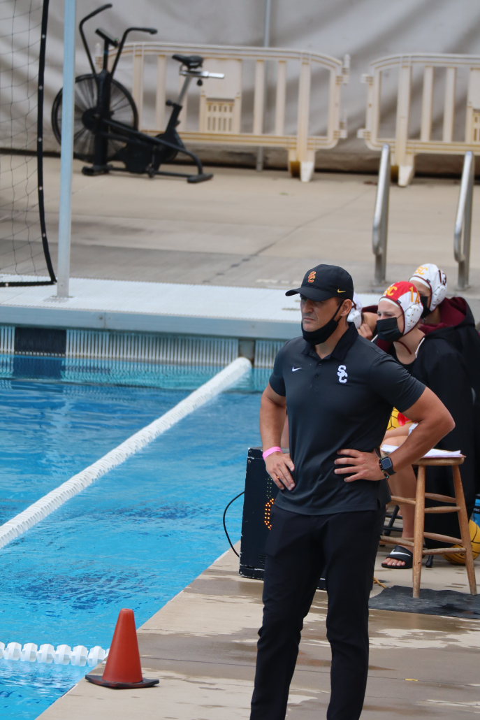 Head coach Marko Pintaric stands on the side of the pool overlooking his team