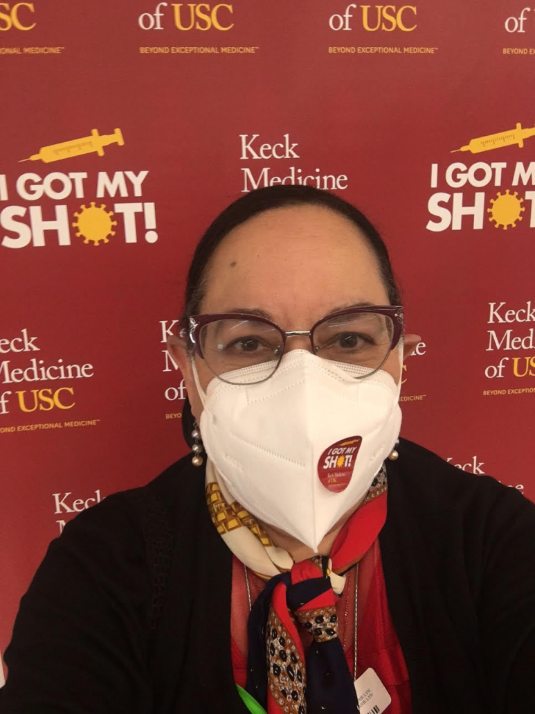 """Photo of Dr. Lourdes Baezconde-Garbanati's posing for a selfie. In the background is a red """"Keck Medicine of USC"""" and """"I Got My Shot"""" poster. Baezconde-Garbanati's also wears a multicolored scarf and a white mask with a """"I Got My Shot"""" sticker on the left side of her mask."""